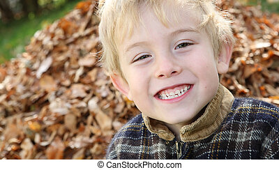 Smiling boy in front of a pile of leaves