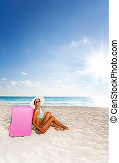 Attractive woman with luggage on the beach