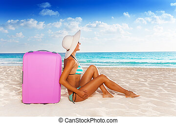 Luggage and beach vacation - Young attractive woman sitting...