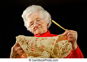 portrait of elderly woman is in red with hook knitting...