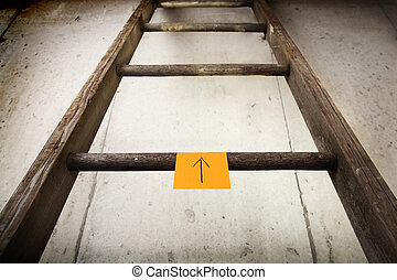 Old wooden ladder on a cement wall - a ladder with a sticky...