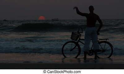 man ride bicycles outdoors by the sea against sunset...