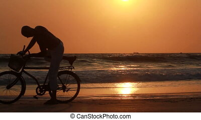man ride bicycles outdoors by the sea against sunset....