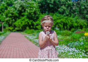 Adorable little girl blowing a dandelion in the park