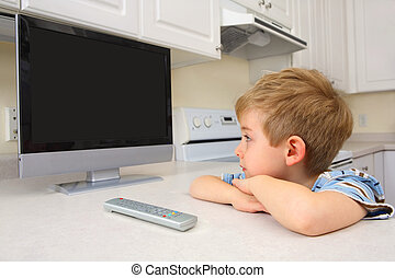 Young boy watching tv in a kitchen