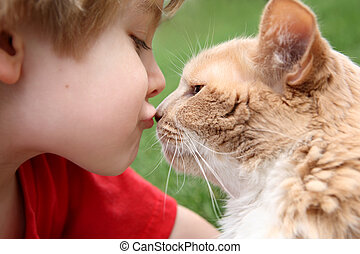 Best friends - a young boy kisses his cat