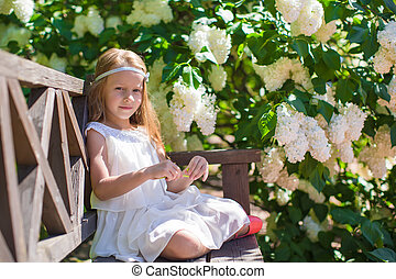 Adorable happy little girl have fun in flower blossoming garden
