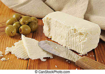 Feta cheese and green olives - A block of feta cheese with...