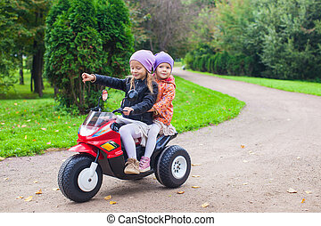 Adorable little girls riding on kid's motobike in the green...