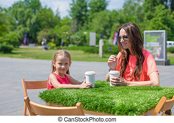 Young mother and her little girl at outdoor cafe on warm day...