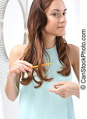 Woman arranges her hair, combing - Hair Styling - brunette...