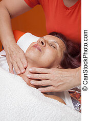 Facial massage, lymphatic drainage - Cute mid aged woman...