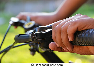 hands holding the handlebars on the bike - detail of the...