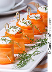 carrot rolls stuffed with soft cheese and dill closeup on a...