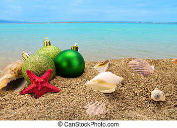 Christmas balls and shells on sand with summer sea...
