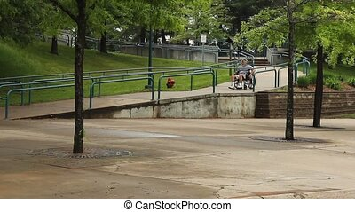 wheelkchair ramp - disabled man using a cement wheelchair...