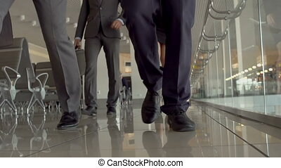 People at Airport Terminal - Four pairs of feet approaching...