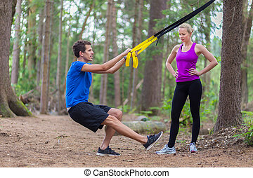 Training with fitness straps outdoors - Young active people...