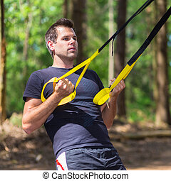 Training with fitness straps outdoors. - Young attractiveman...