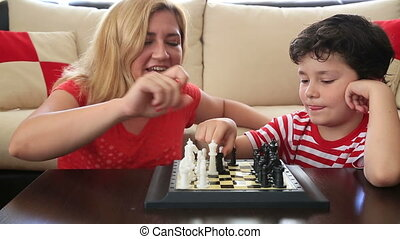 Mother and son playing chess at home
