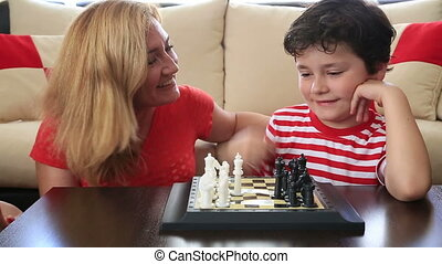 Mother teaches son how to play ches - Mother and son playing...