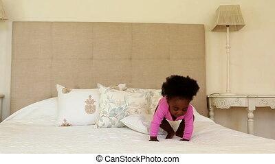 Cute baby girl standing and clapping on bed at home in...