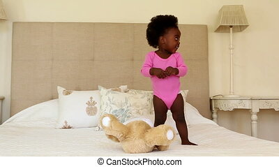 Cute baby girl playing and clapping on bed at home in...