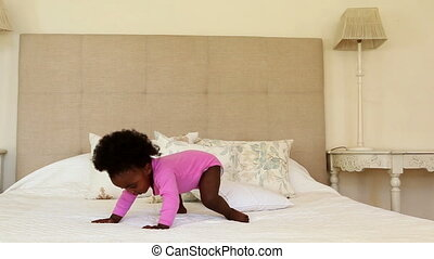 Cute baby girl standing and falling on bed at home in...