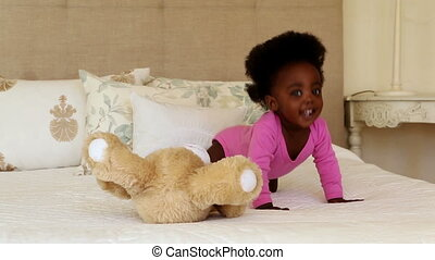 Cute baby girl playing with teddy bear on bed at home in...