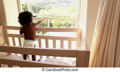 Cute baby girl standing in her crib looking out window at...