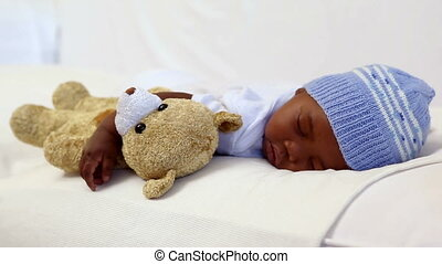 Baby boy sleeping in crib with teddy bear at home in bedroom