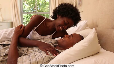 Cute couple lying on a bed at home in bedroom