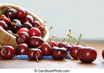 many cherries in a wooden bowl on a table