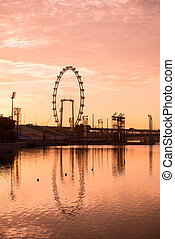 Silhouette of big ferris wheel in pink sky - Silhouette of...