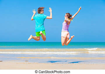 Back view of happy young couple jumping at beach