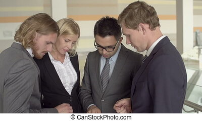Business Team - Tilt up from digital tablet to faces of four...