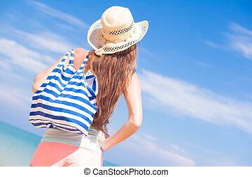back view of a woman with stripy bag and straw hat at...