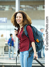 Woman smiling with luggage at airport - Portrait of a...