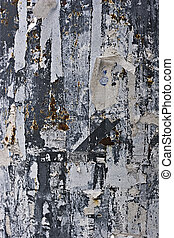 torn paper on a metal wall - leftovers of torn paper on a...