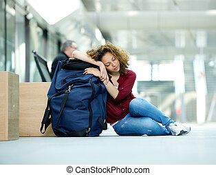 Young woman sleeping at airport - Portrait of a tired young...