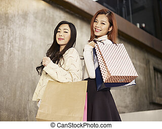 women with shopping bags - young asian women with shopping...