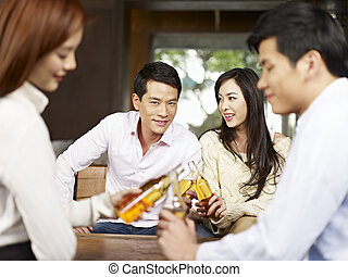 having a good time - two young asian couples drinking beer...