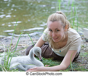 The young woman near a baby bird of a swan on the bank of...