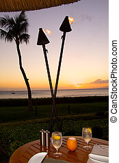 Sunset Dinner Table - a dinner table set on the beach at...