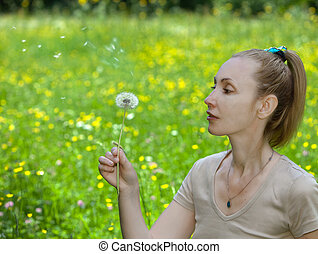 The young attractive woman blows off fuzzes from a dandelion