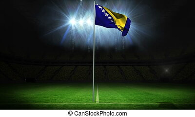Bosnia national flag waving on flagpole against football...