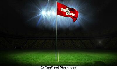 Swiss national flag waving on flagpole against football...