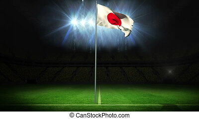 Japan national flag waving on flagpole against football...