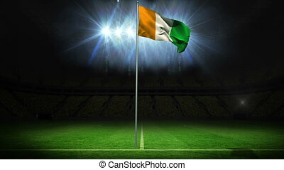 Ivory coast national flag waving on flagpole against...
