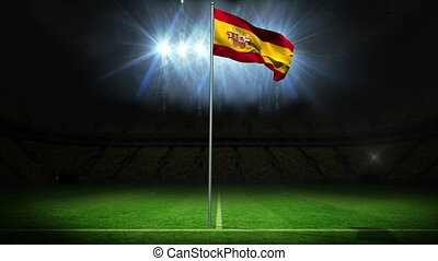 Spain national flag waving on flagpole against football...
